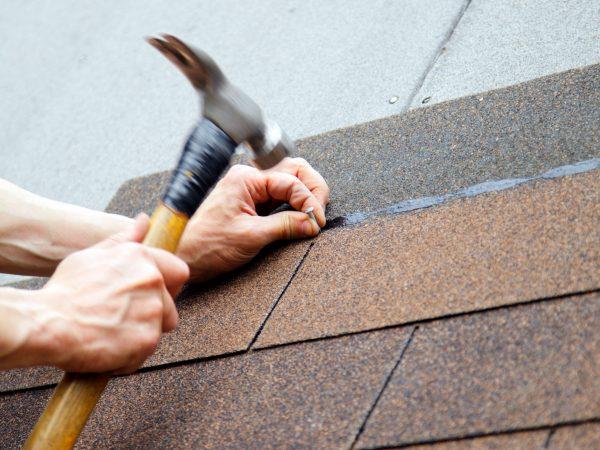 roofer installing composite shingles