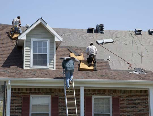Roofing contractors on a red composite roof