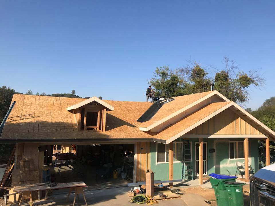 new roof being installed by kelly roofing contractors is in the final stages of installation on a beautiful blue day in Salida, California residential suburb