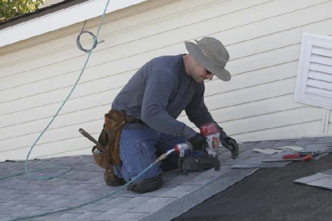 shingles being applied to roof of a residential house by kelly roofing contractor